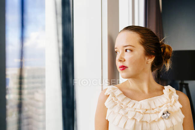 Thoughtful woman standing by window — Stock Photo