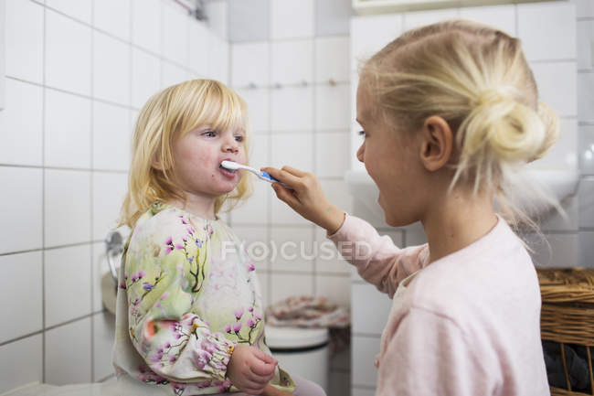 Sister brushing girls teeth — Stock Photo