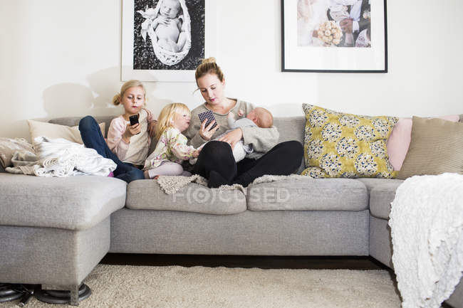 Girls sitting by mother on sofa — Stock Photo
