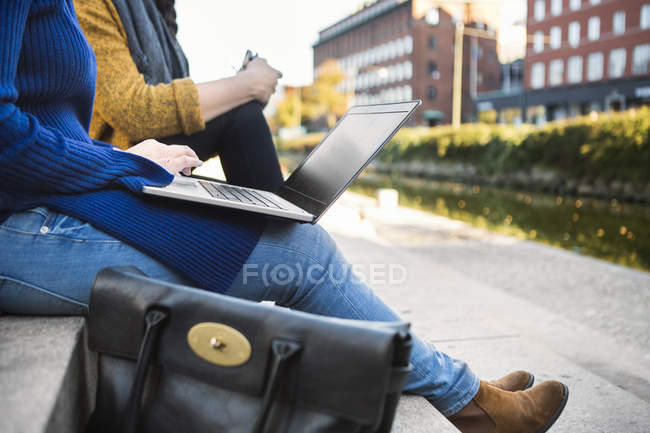 Colleagues sitting on steps and using laptops — Stock Photo