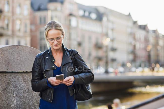 Femme mature utilisant un téléphone intelligent — Photo de stock