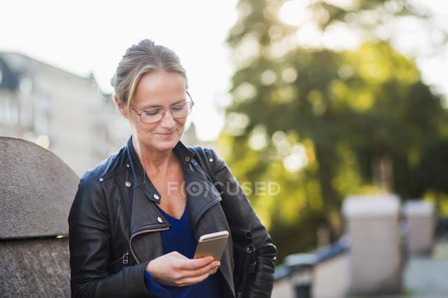 Femme mûre regardant le téléphone intelligent — Photo de stock