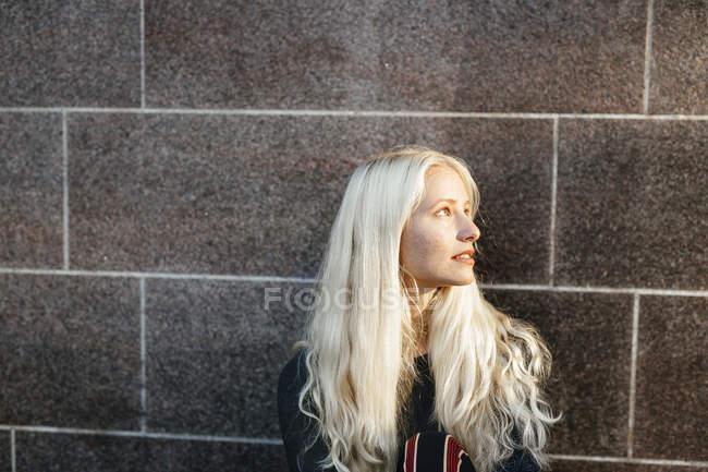 Ragazza guardando lontano contro il muro — Foto stock