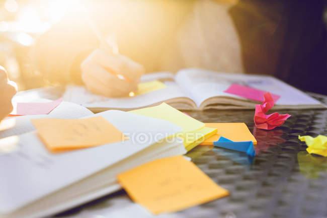 Подросток пишет книгу на столе — стоковое фото