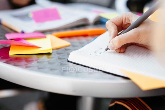 Mão a escrever sobre o livro no café de calçada — Fotografia de Stock