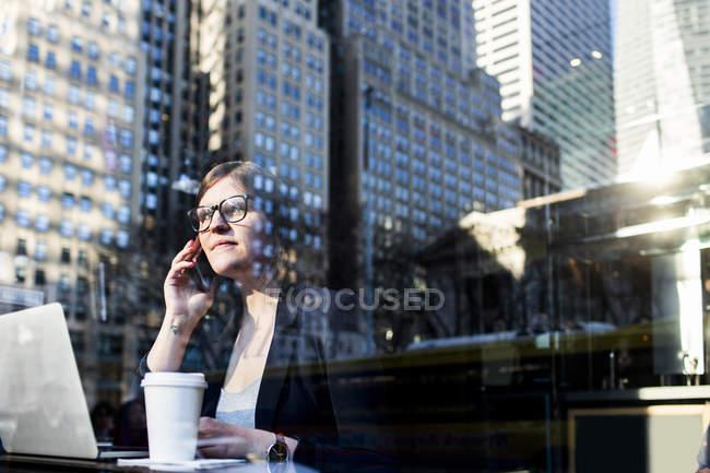 Femme d'affaires utilisant le téléphone vu par la fenêtre — Photo de stock
