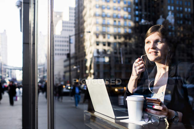 Businesswoman with headphones using laptop — Stock Photo
