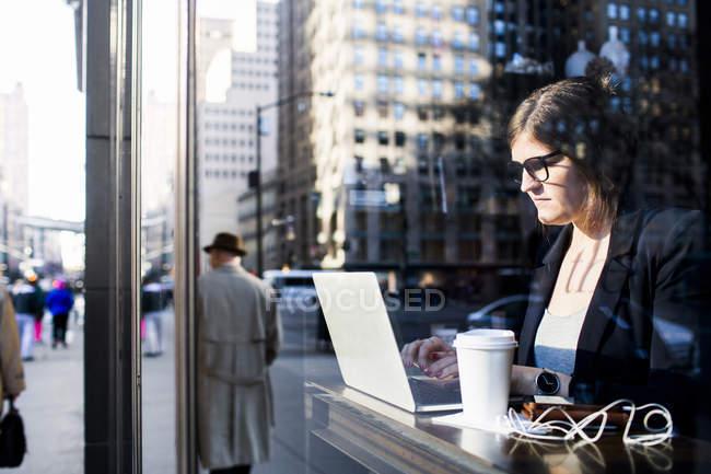 Donna d'affari che utilizza il computer portatile mentre seduto alla caffetteria — Foto stock