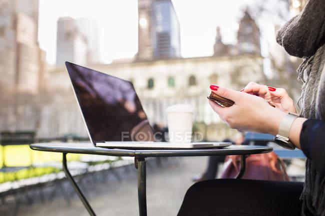 Mujer con portátil y teléfono inteligente - foto de stock
