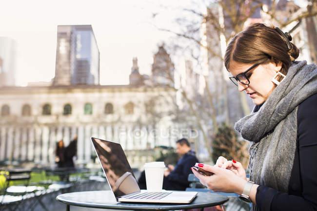 Mujer de negocios usando el teléfono mientras está sentada en la mesa - foto de stock