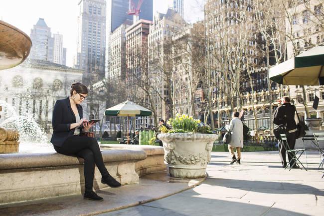 Donna d'affari che utilizza tablet mentre seduto contro fontana — Foto stock