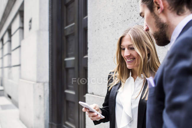 Business woman showing smartphone to man — стоковое фото