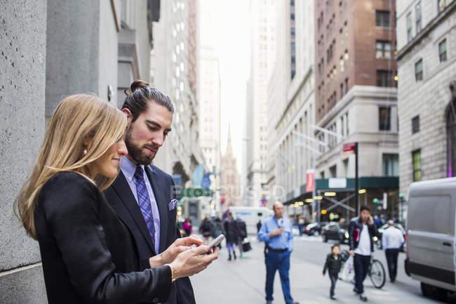 Mujer mostrando teléfono a hombre de negocios - foto de stock