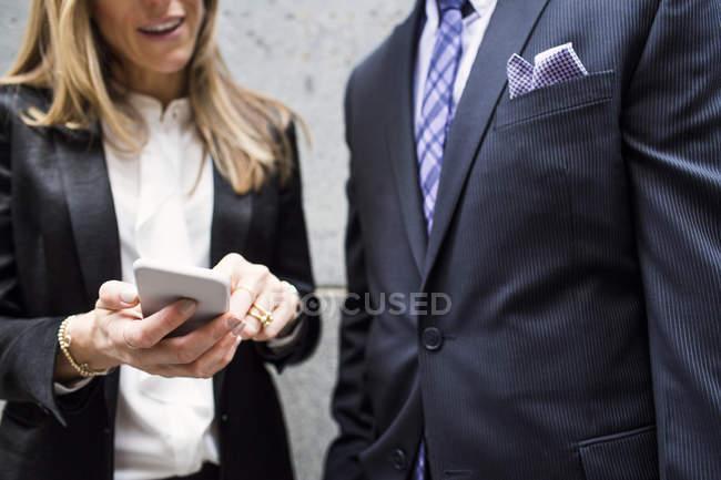 Hombre de negocios y mujer de negocios de pie con teléfono inteligente - foto de stock