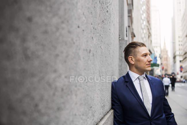 Uomo d'affari appoggiato al muro sul marciapiede — Foto stock
