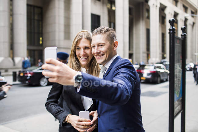Business man and woman taking selfie — стоковое фото