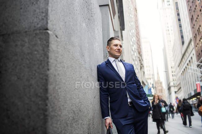 Uomo d'affari appoggiato al muro — Foto stock