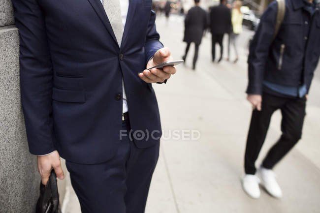 Businessman using phone while leaning on wall — Stock Photo