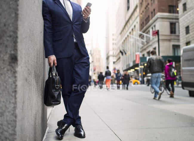 Uomo d'affari che tiene la borsa e l'utilizzo di smartphone — Foto stock