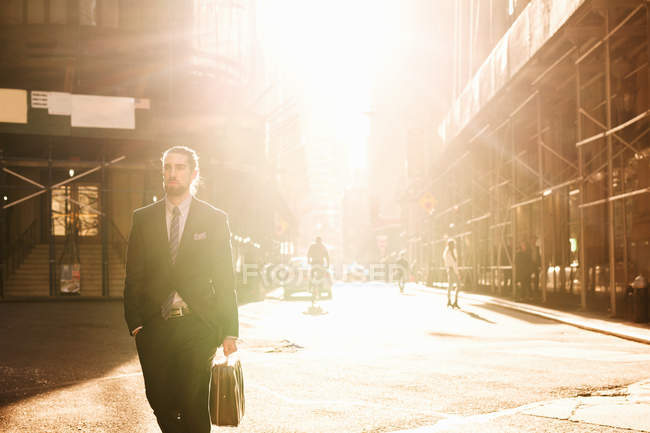 Homme d'affaires avec mallette marchant dans la rue de la ville — Photo de stock