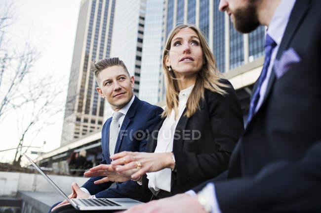 Businesswoman explaining colleagues using laptop — Stock Photo