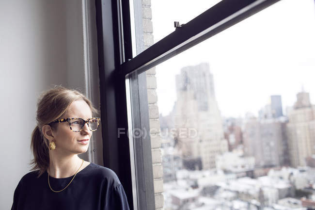 Donna d'affari guardando attraverso la finestra — Foto stock