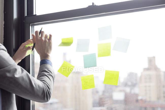 Uomo d'affari attaccare nota sulla finestra di vetro — Foto stock