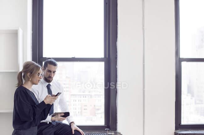Geschäftsfrau zeigt Handy an Mann — Stockfoto