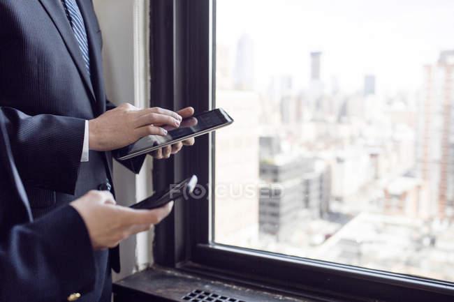 Hombre de negocios y mujer de negocios por ventana - foto de stock