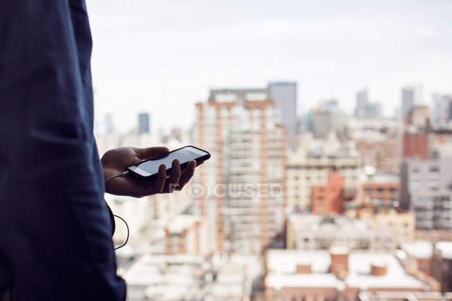 Geschäftsmann hält Telefon mit Gebäuden, die durch Fenster gesehen — Stockfoto