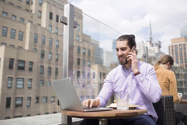 Uomo d'affari che parla al telefono mentre utilizza il computer portatile — Foto stock