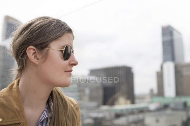 Femme d'affaires, lunettes de soleil permanent contre les bâtiments — Photo de stock