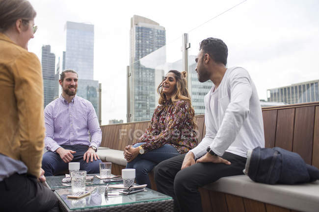 Friends relaxing at rooftop restaurant — Stock Photo