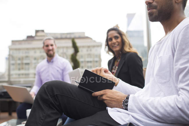Businessman with colleagues at restaurant — Stock Photo