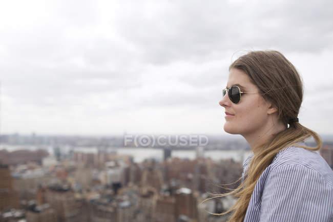 Donna guardando la città contro il cielo — Foto stock