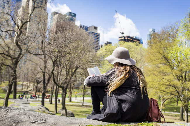 Woman reading book while sitting on rock — Stock Photo