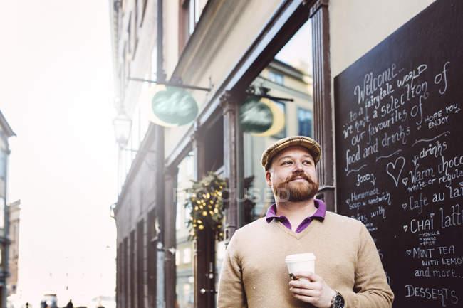 Uomo in piedi di fronte al caffè — Foto stock