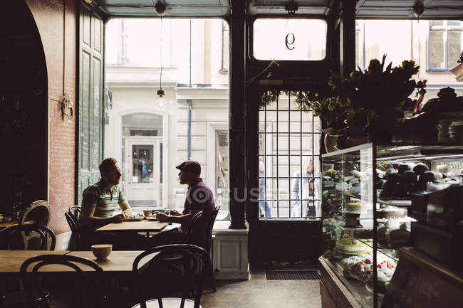 Due uomini che mangiano caffè in caffè — Foto stock