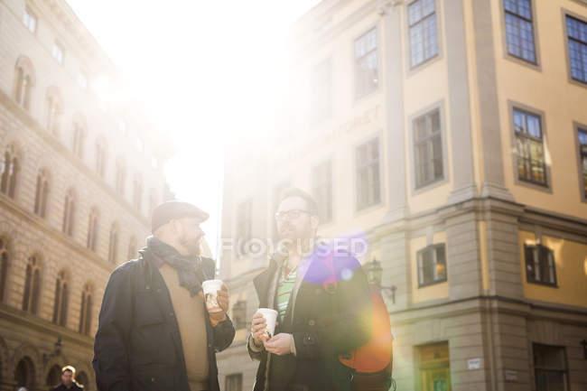 Двое мужчин пьют кофе на улице — стоковое фото