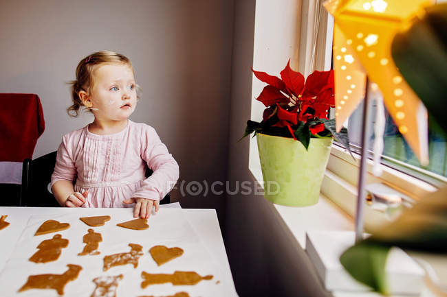 Girl looking through window at home — Stock Photo