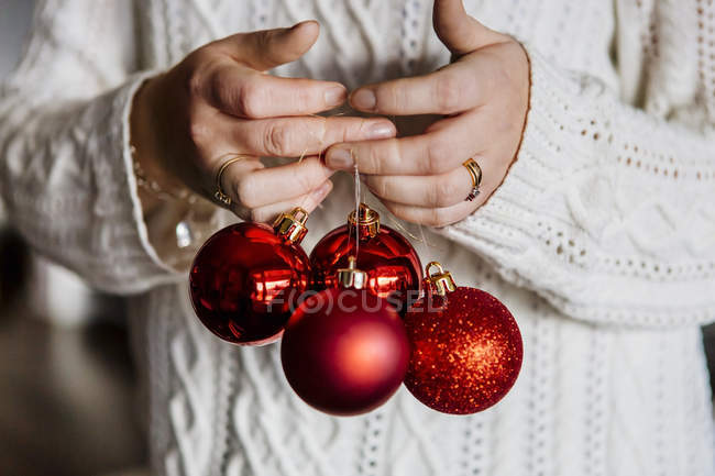 Woman holding red Christmas baubles — Stock Photo