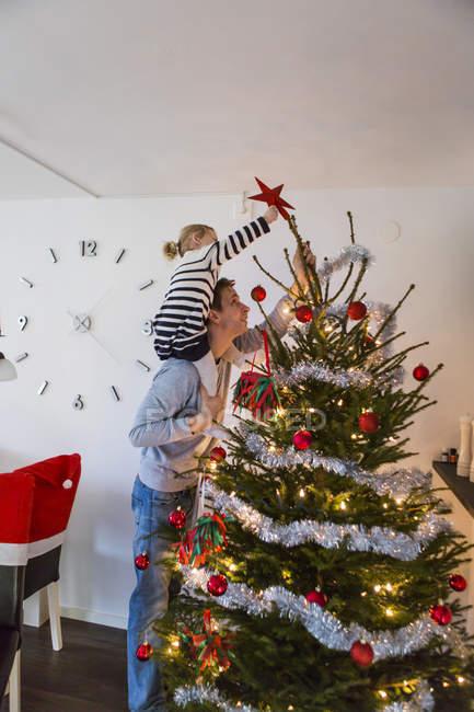 Padre e hija decorando el árbol de las christmas. - foto de stock
