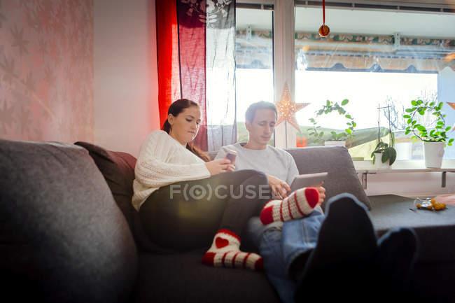 Coppia utilizzando tablet e smartphone — Foto stock