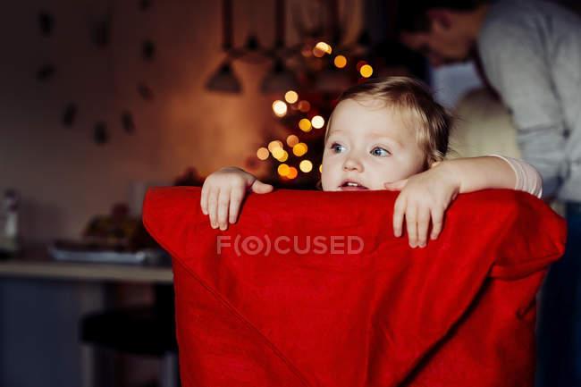 Garota de pé na cadeira de tecido vermelho coberto — Fotografia de Stock
