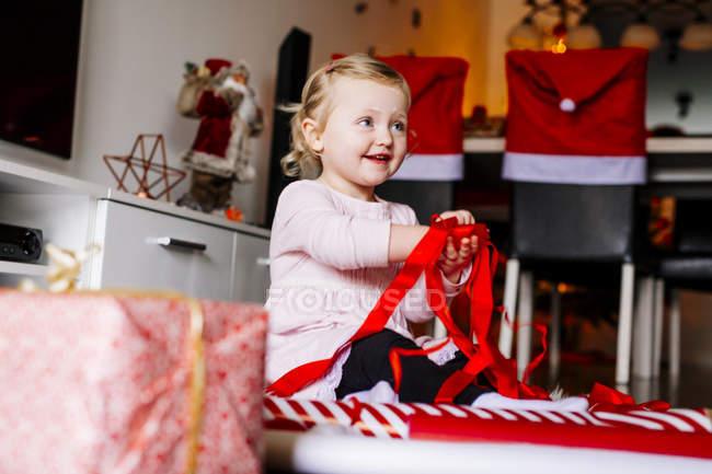 Linda garota brincando com fitas vermelhas — Fotografia de Stock