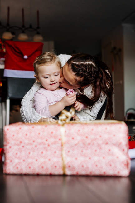 Mother kissing daughter during Christmas — Stock Photo