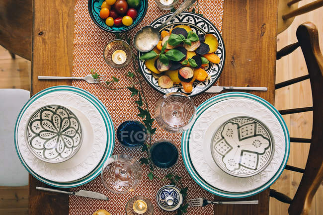 Plates and bowls on laid table — Stock Photo