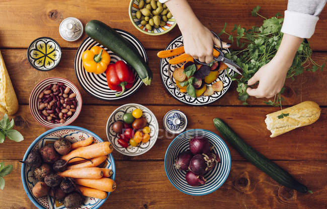 Hand cutting vegetables at wooden table — Stock Photo