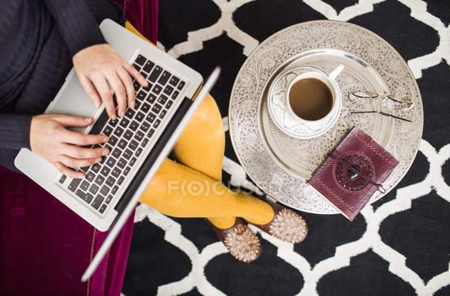 Woman using laptop while having coffee — Stock Photo