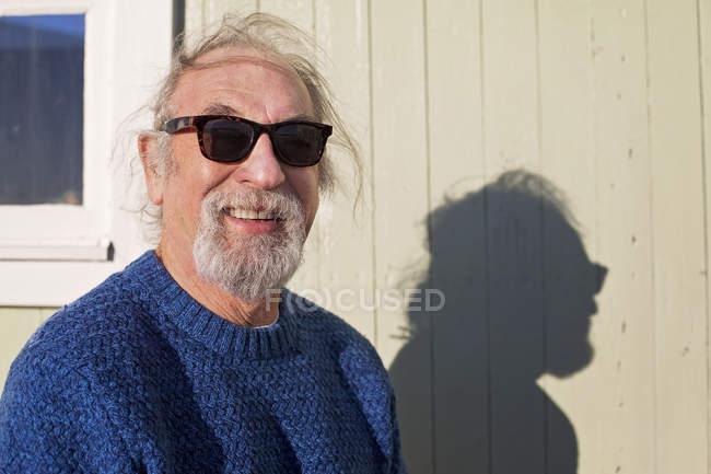 Man wearing sunglasses standing against beach hut — Stock Photo